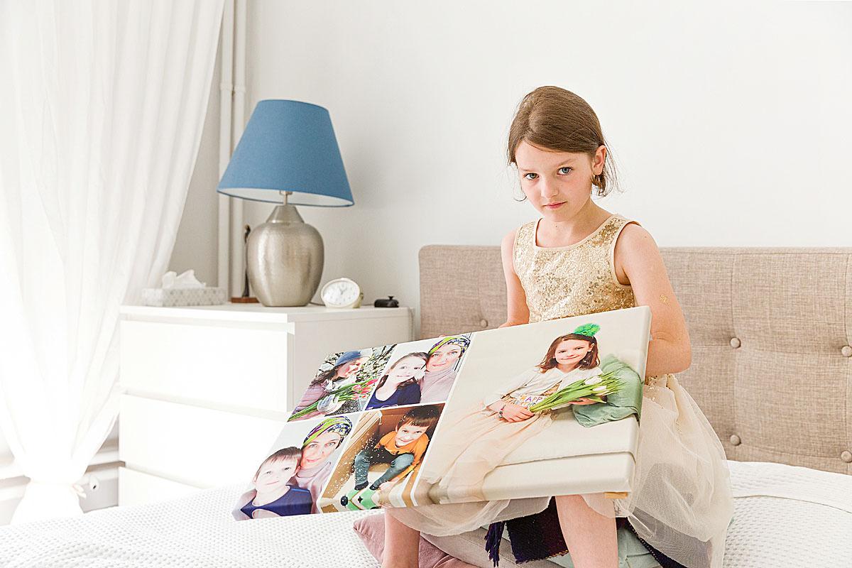 Dziewczynka pokazuje prezent w postaci fotokolażu z wielu zdjęć