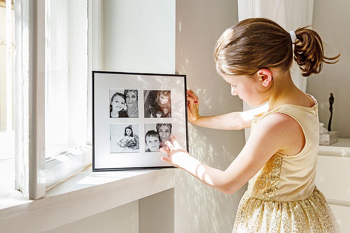 Dziewczynka wpatrująca się w rodzinny fotoobraz oparty przy oknie w salonie