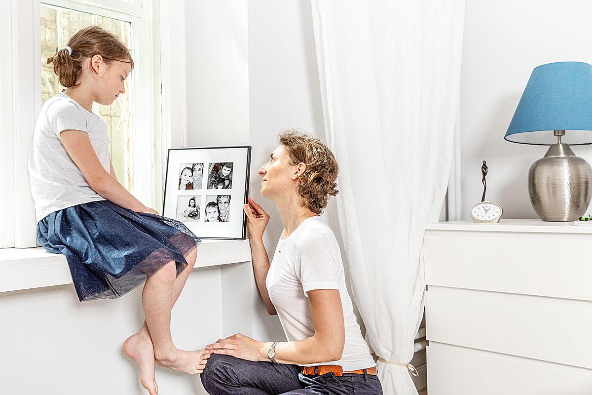 Mama pokazująca córce rodzinne zdjęcia na fotoobrazie