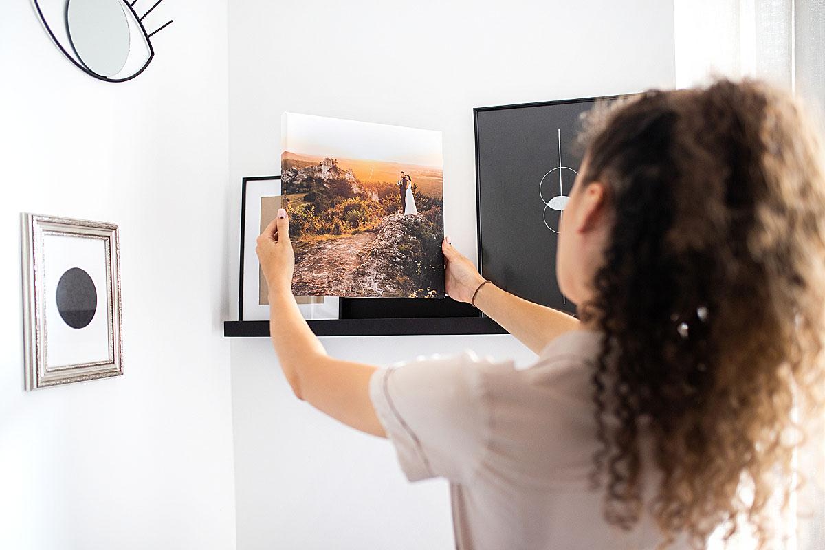 kobieta przymierzająca obraz ślubny do ściany