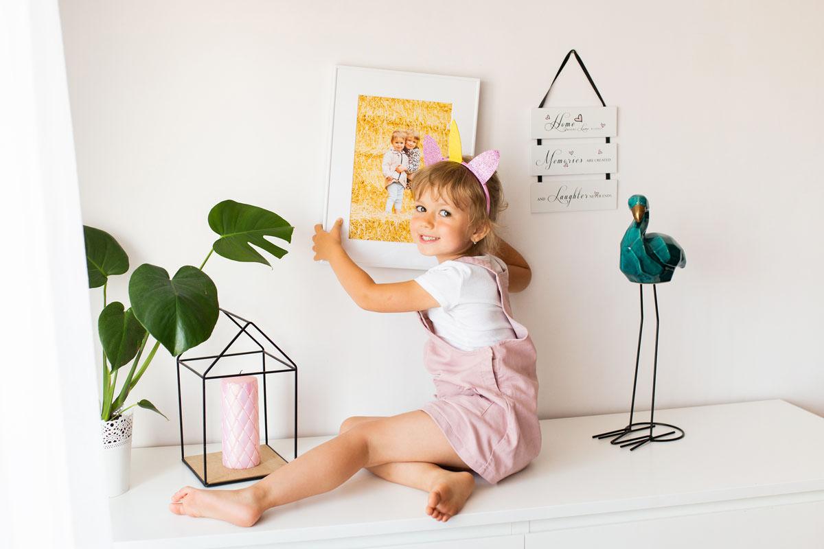 dziewczynka-wieszajaca-obraz-w-ramce