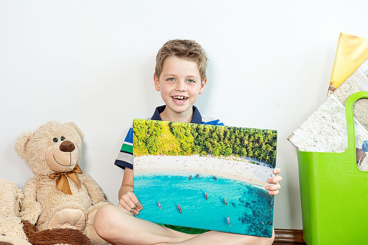 Syn chwali się wydrukowanym kolorowym obrazem na płóntie z wakacji