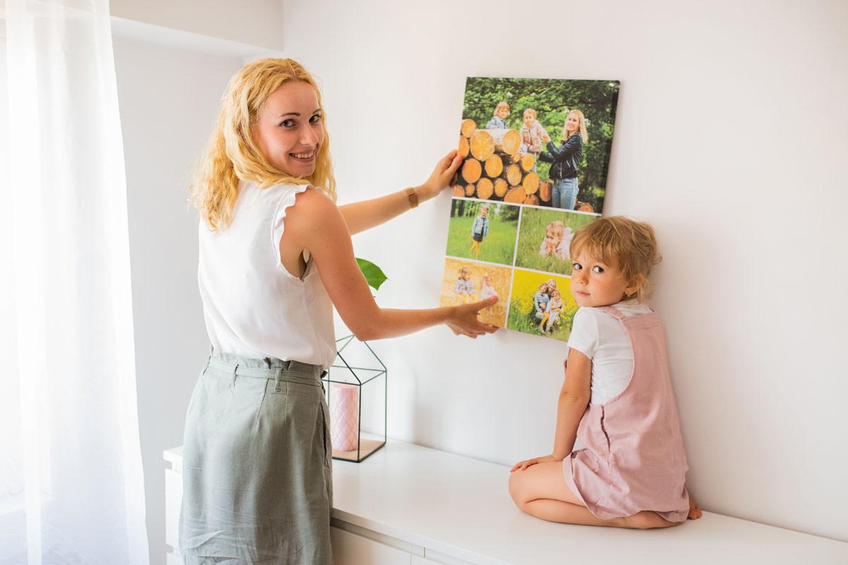 Mama z córką wieszająca rodzinny fotoobraz kolaż zdjęć