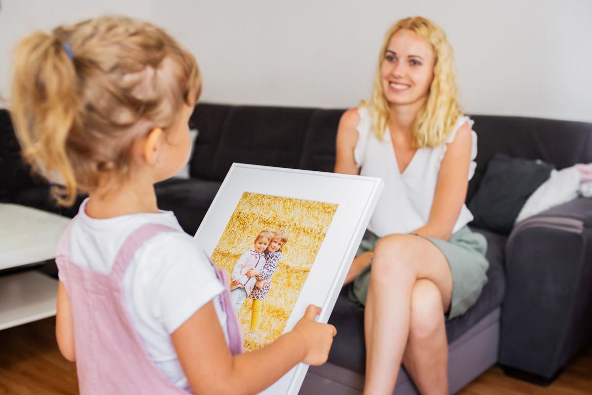 Córka wręczająca mamie fotoobraz w ramce na prezent