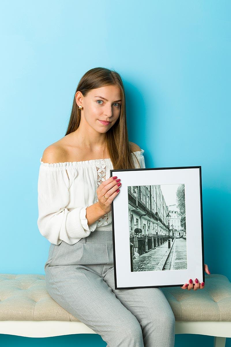 Dziewczyna siedzi z fotoobrazem w czarnej ramce