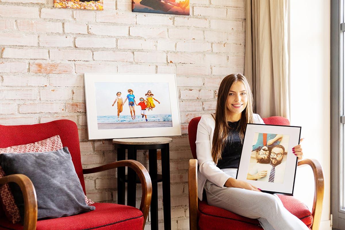 Dziewczyna trzymająca portret na fotoobrazie w ramce