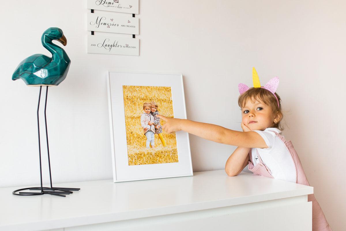 Dziewczynka pokazująca swojego brata na obrazie w ramce