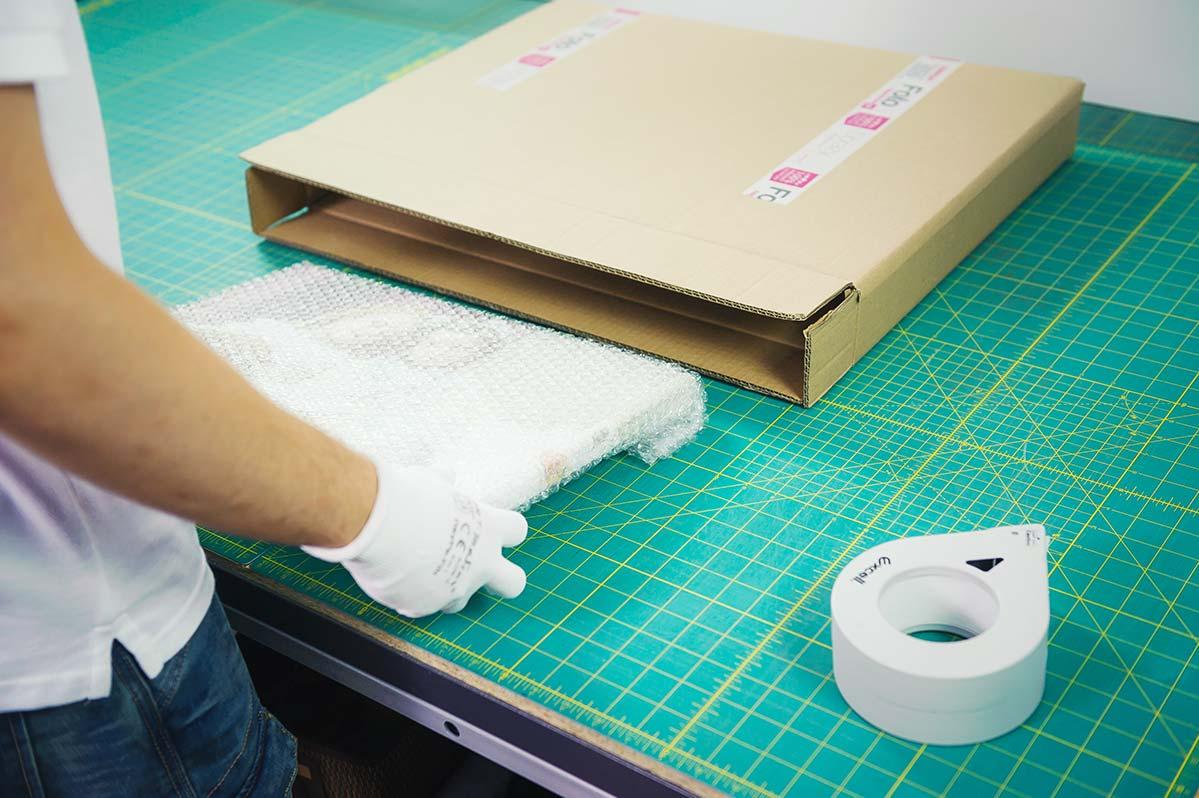 Pracownik wkładający obraz na płótnie do kartonu