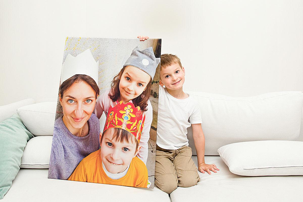 Chłopak chwali się portretem rodzinnym wydrukowanym na płótnie