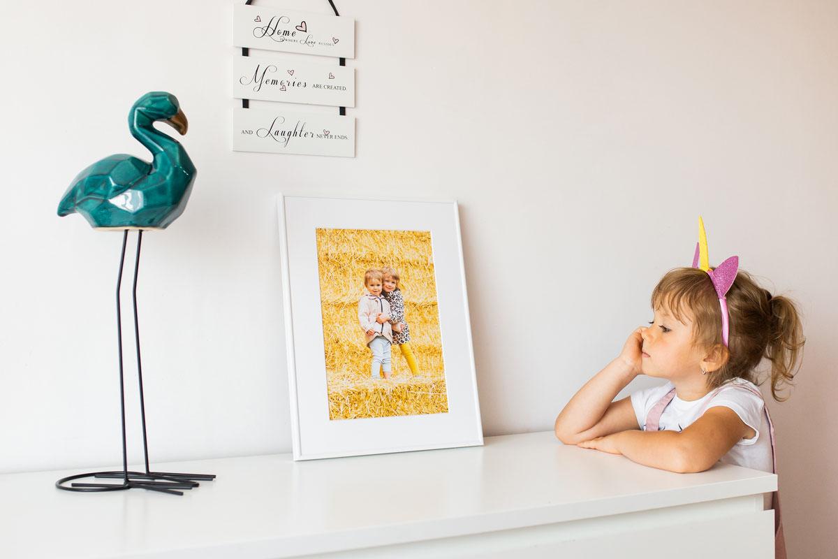 Dziecko patrzące na portret swój i brata
