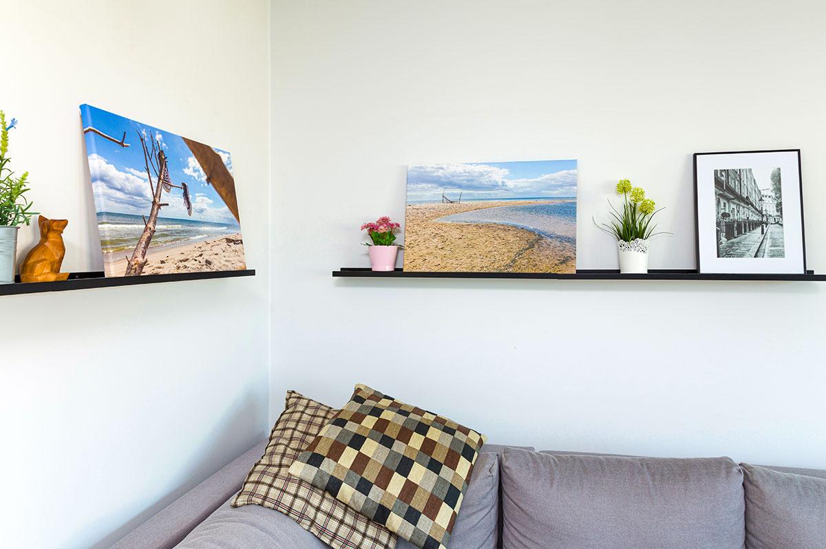 Fotoobrazy wakacyjne stojące na półce nad sofą
