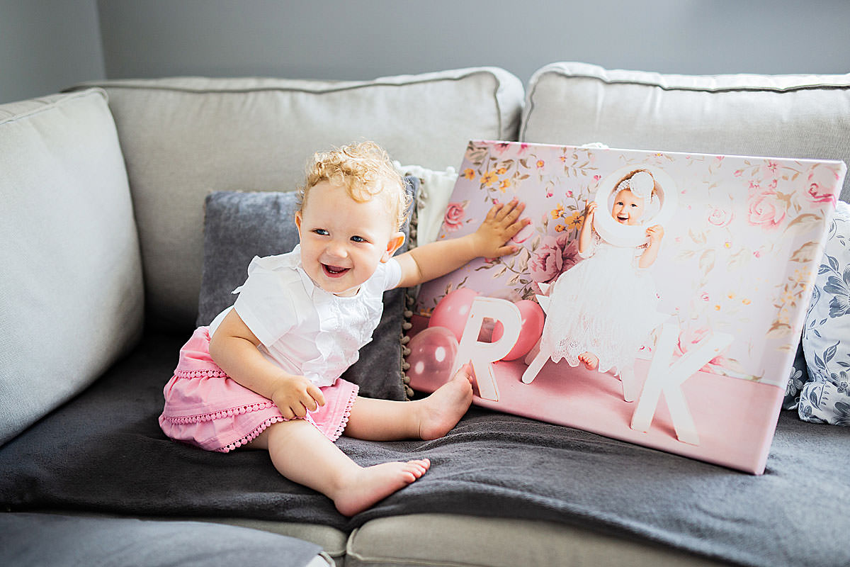 Małe dziecko siedzi na sofie i ogląda swój portret na płótnie