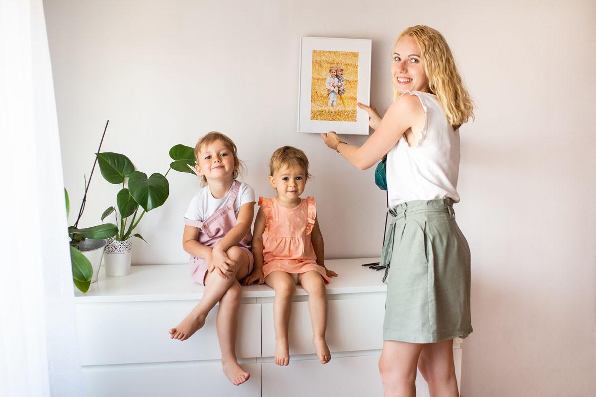Mama zawieszająca na ścianie portret dzieci