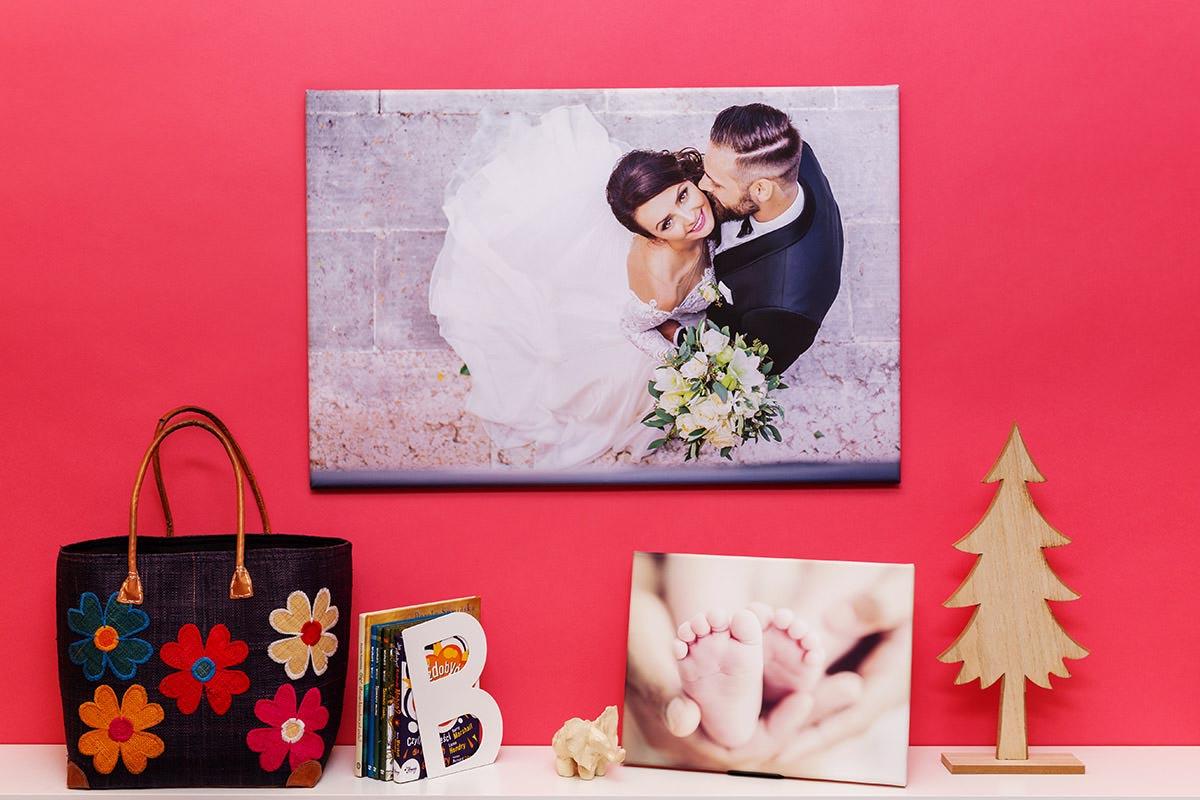Portret ślubny wisi na czerwonej ścianie a obok portret dziecka