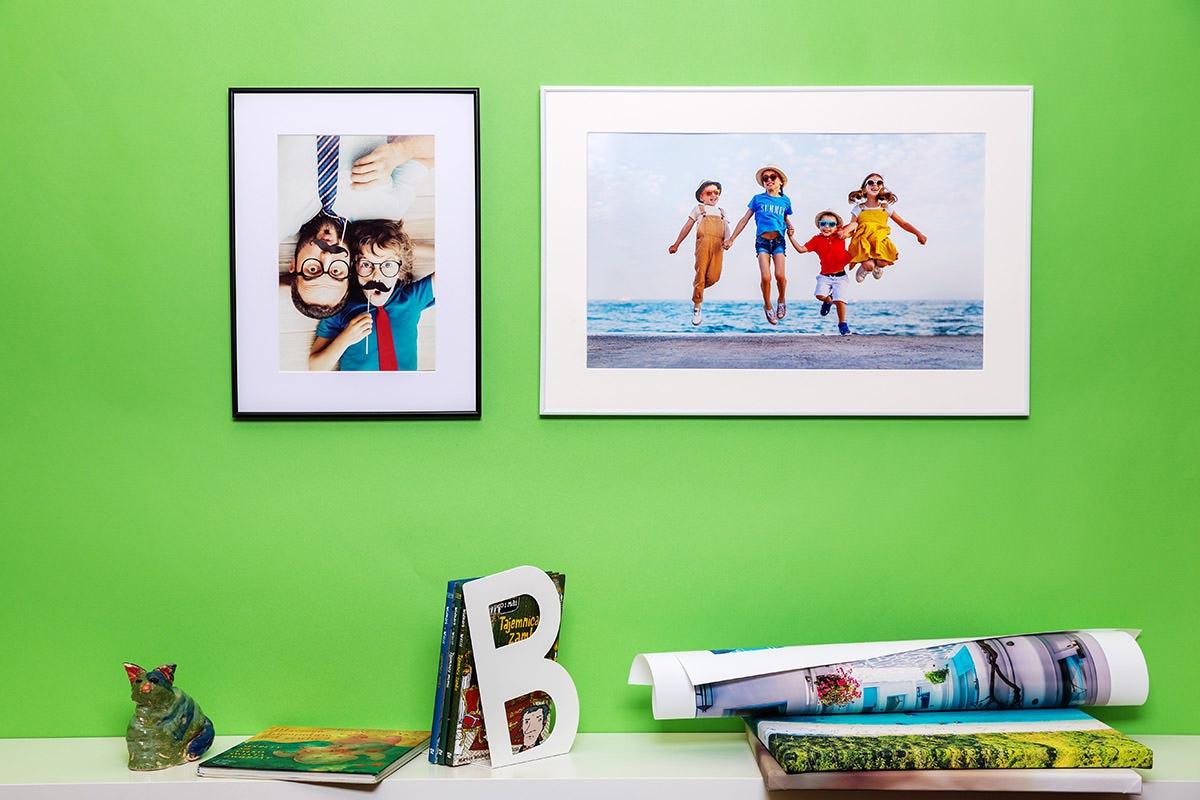 Rodzina na dwóch obrazach w ramkach wisi na zielonej ścianie pokoju
